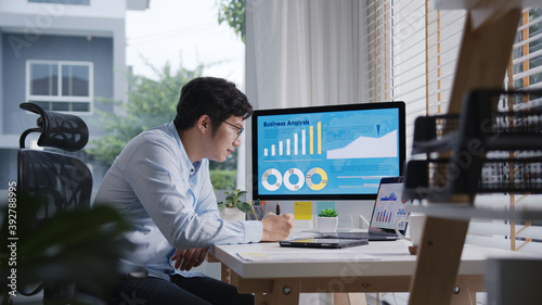 Fototapeta Candid of young attractive asian thai man busy work multiple screen computer or smart tablet on table desk at home in freelance data analyst, data science scientist for business. obraz