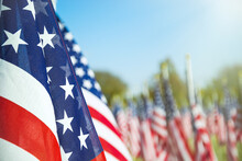 Closeup Of An American Flag In A Row. Blue Sky And Flags In The Background. Copy Space.