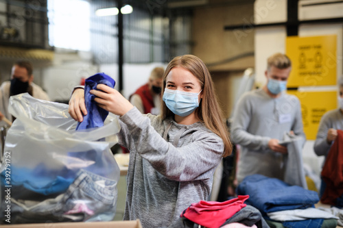 Obraz Volunteers sorting out donated clothes in community charity donation center, coronavirus concept. - fototapety do salonu