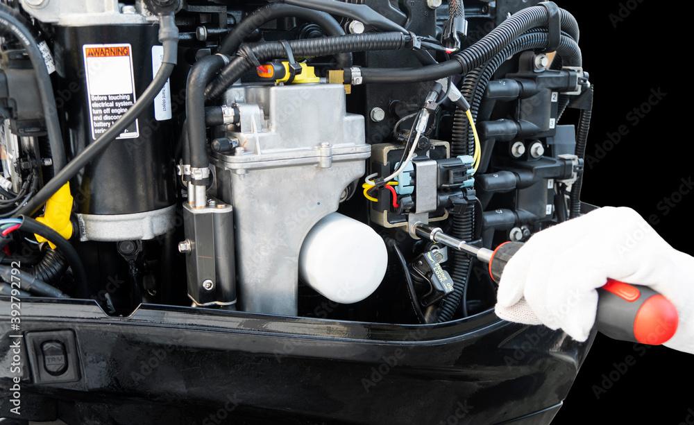 Fototapeta Repairing  outboard marine engine. Motorboat engine seasonal service and maintenance. Mechanic hand performing maintenance on outboard engine