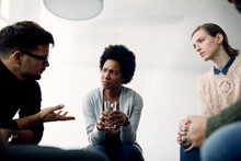 Group Of People Talking Among Themselves During Therapy Meeting.