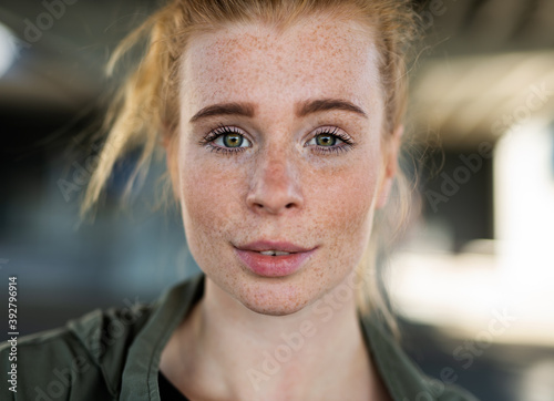 Obraz Close-up portrait of young woman with red hair outdoors in town, looking at camera. - fototapety do salonu
