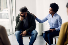 Black Female Therapist Supporting A Man Who Is Talking Abut His Issues During Group Meeting.