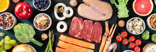 Fototapeta Food panorama, top shot. Beef, chicken, salmon, rice, cheese, fruit and vegetables, an assortment of fresh products on a dark blue wooden background obraz