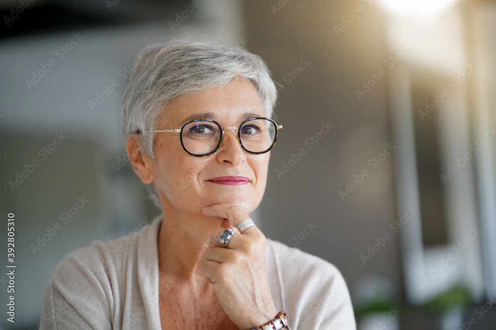 Fototapeta Portrait of a attractive smiling 55-year-old woman with white hair