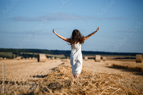 Fényképezés Young curly-haired woman in a wheat field, where there is a huge sheaf of hay, enjoying nature