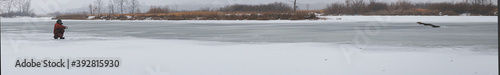 Fotografija A fisherman sits on the ice of a frozen river and catches fish