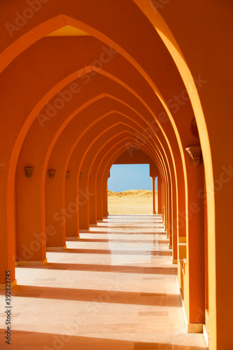 Canvastavla Colorful orange arched hallway passage with columns leading to a desert on a sunny day