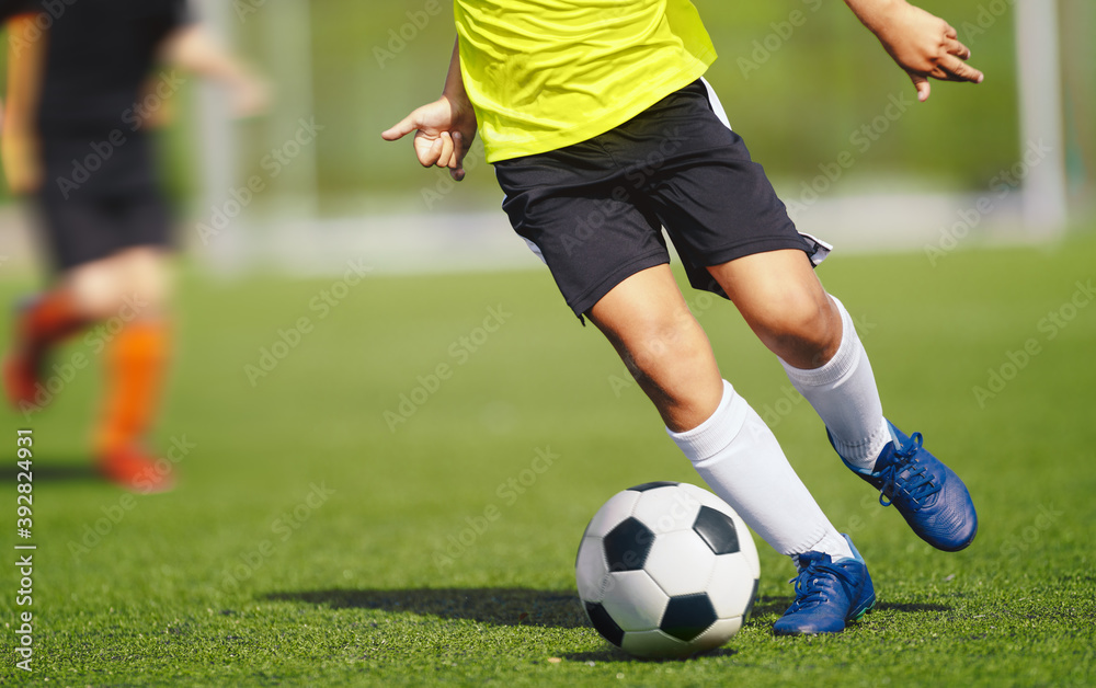 Fototapeta Young boy in yellow soccer jersey uniform running after ball on training pitch. Kid improving dribbling skills on practice session
