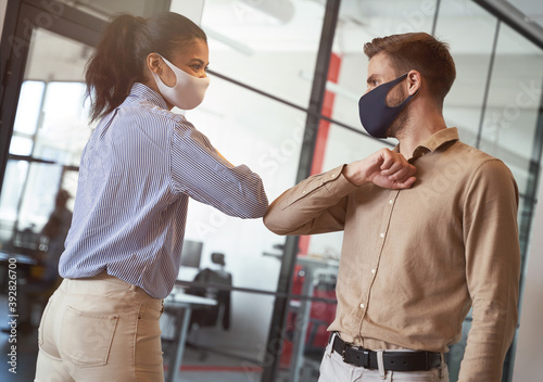 Obraz Two young diverse business colleagues wearing face protective masks bumping elbows, greeting each other while working during covid 19 quarantine - fototapety do salonu