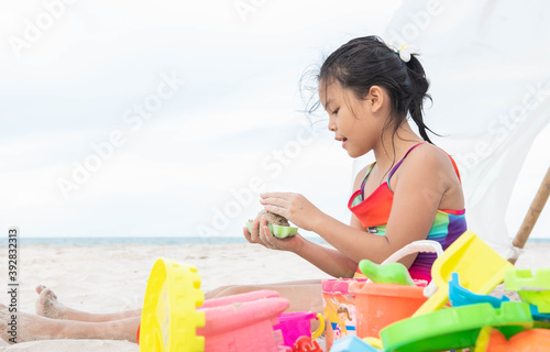 cute little girl playing on the beach on summer holidays Fototapet