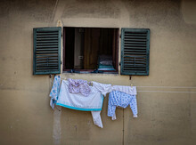 Washing Hanging Underneath A Window With Shutters In The Mediterranean.
