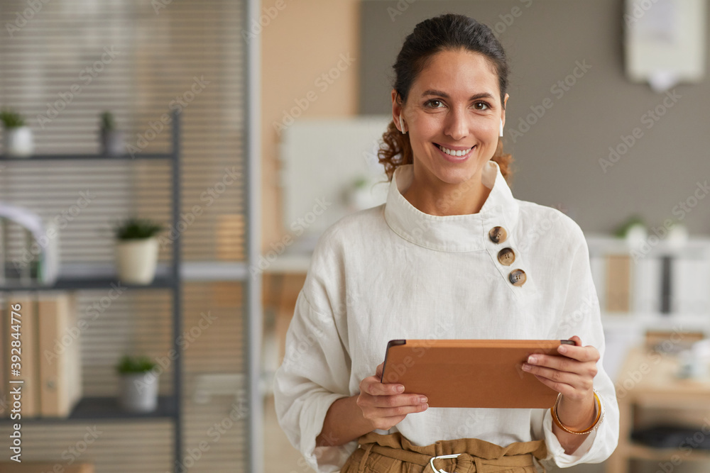 Fototapeta Waist up portrait of elegant modern businesswoman holding tablet and looking at camera with wireless earphones while standing in office, copy space