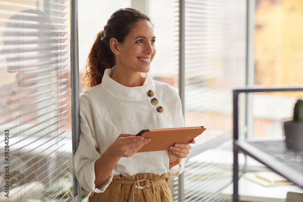Fototapeta Waist up portrait of smiling successful businesswoman holding digital tablet and looking away while working in office, copy space