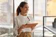 Leinwandbild Motiv Waist up portrait of smiling successful businesswoman holding digital tablet and looking away while working in office, copy space