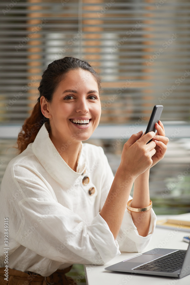Fototapeta Vertical portrait of smiling elegant woman looking at camera and holding smartphone while enjoying work from home