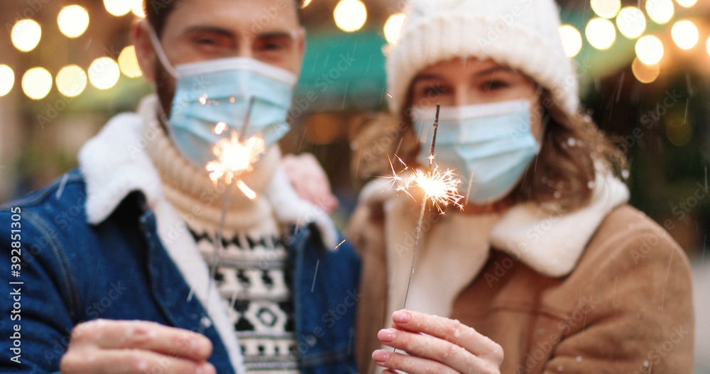 Leinwandbild Motiv - VAKSMANV : Close up of Caucasian happy couple holding sparklers while standing on decorated xmas street in medical masks in quarantine. Joyful man and woman celebrating new year 2021. Holiday celebration concept