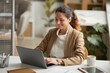 Leinwandbild Motiv Portrait of relaxed elegant businesswoman smiling happily and using laptop while enjoying work in office, copy space