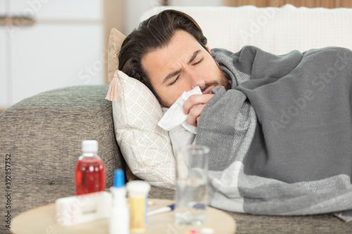 Fotografía sick man with flu lying in sofa at home