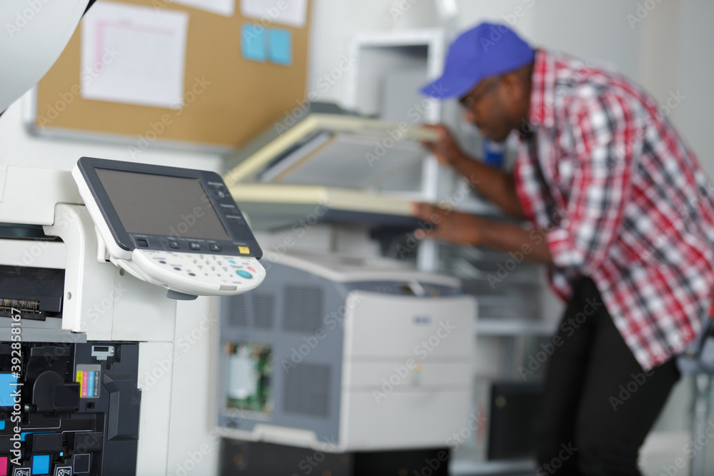 Fototapeta male technician repairing digital photocopier machine