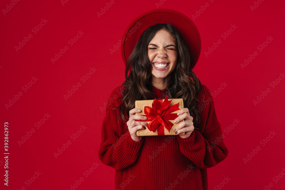 Fototapeta Excited beautiful brunette girl in hat smiling and posing with gift box