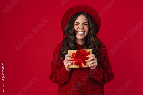 Fototapeta Excited beautiful brunette girl in hat smiling and posing with gift box obraz