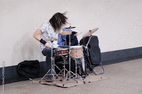 Male musician drummer playing a musical instrument at a public transport station Fototapet
