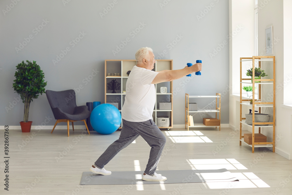 Fototapeta Active, sporty, healthy senior man doing fitness exercise with dumbbells at home
