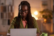 Leinwandbild Motiv Front view portrait of young African-American woman using laptop while working in office or at home lit by cozy dim lighting, copy space