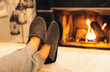 Man in slippers relaxing with his feet up - warm cozy cabin scene with a fireplace in the background.