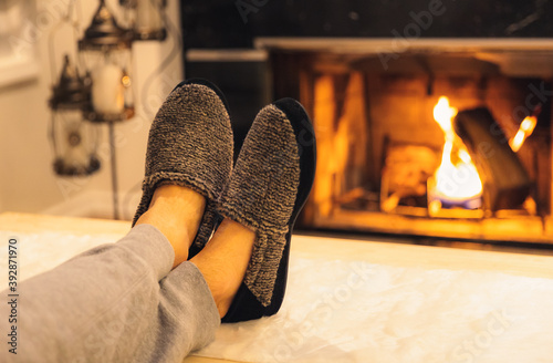 Fototapeta Man in slippers relaxing with his feet up - warm cozy cabin scene with a fireplace in the background