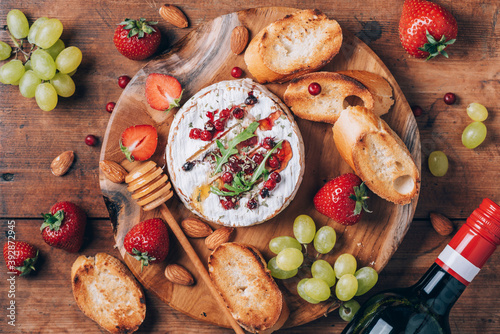 Romantic date night. Valentine's Day, love concept. Baked camembert cheese with honey, rucola, cranberry, wine, toasted bread, grape, strawberries, almond nuts on wooden board. Top view. Copy space