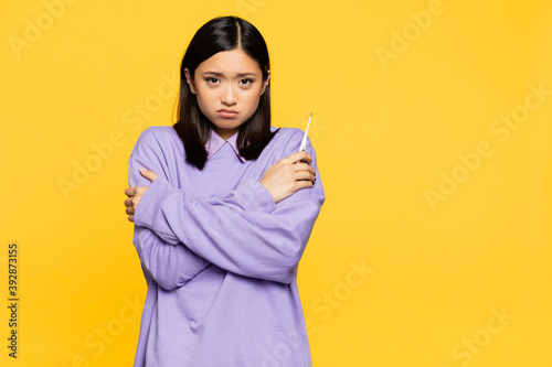 Cuadros en Lienzo sick asian woman holding digital thermometer while freezing isolated on yellow