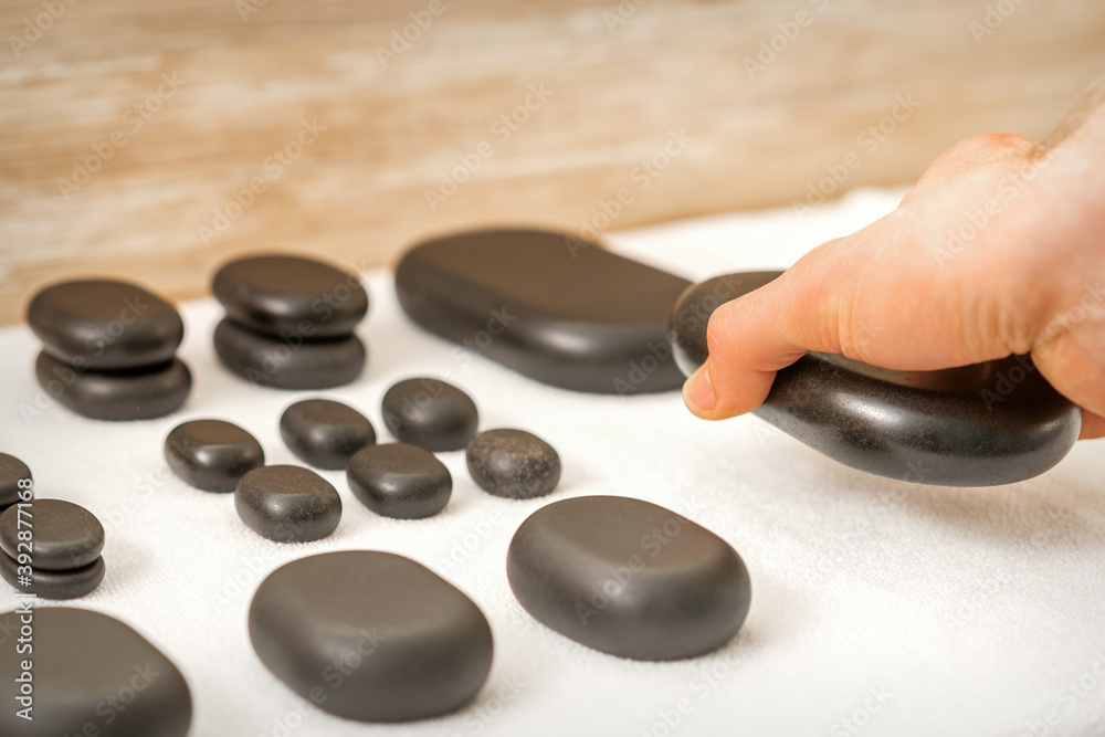 Fototapeta Hand of masseur lays out massage stones on the table in spa salon