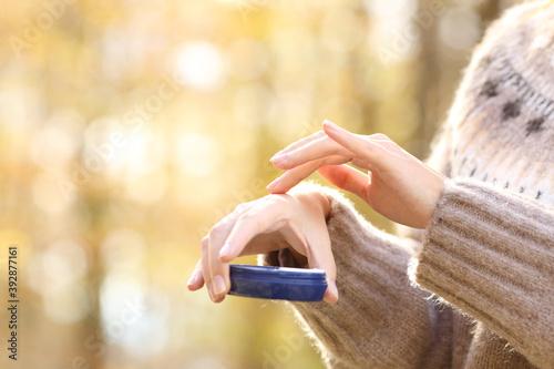 Cuadros en Lienzo Woman with dry skin applying moisturizer cream in autumn