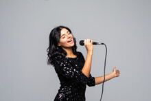 Beautiful Brunette Woman Singing To Microphone Isolated On Gray Background