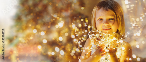 Fotografie, Obraz little girl with christmas lights looks at the camera