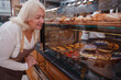 Lovely mature female baker examining her retail display at her bakery store