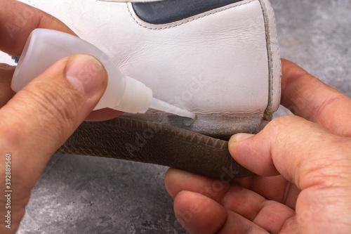 Obraz Repairing sneakers with glue. Repair of shoe soles. - fototapety do salonu