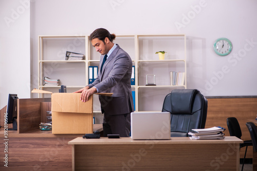 Fototapeta Young male employee being dismissed from his work