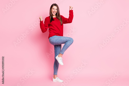 Full length photo of charming lady open mouth raise arms knee wear red sweater jeans sneakers isolated pink color background