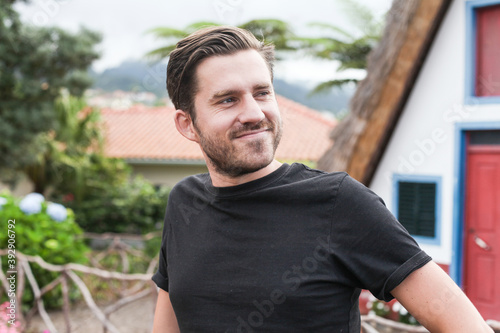 Photo A young man in a black t-shirt smiling and looking aside, outdoors