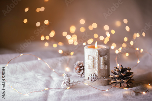 Natural Christmas decoration with burning candle on white linen and pine cones  -  magic lights in background