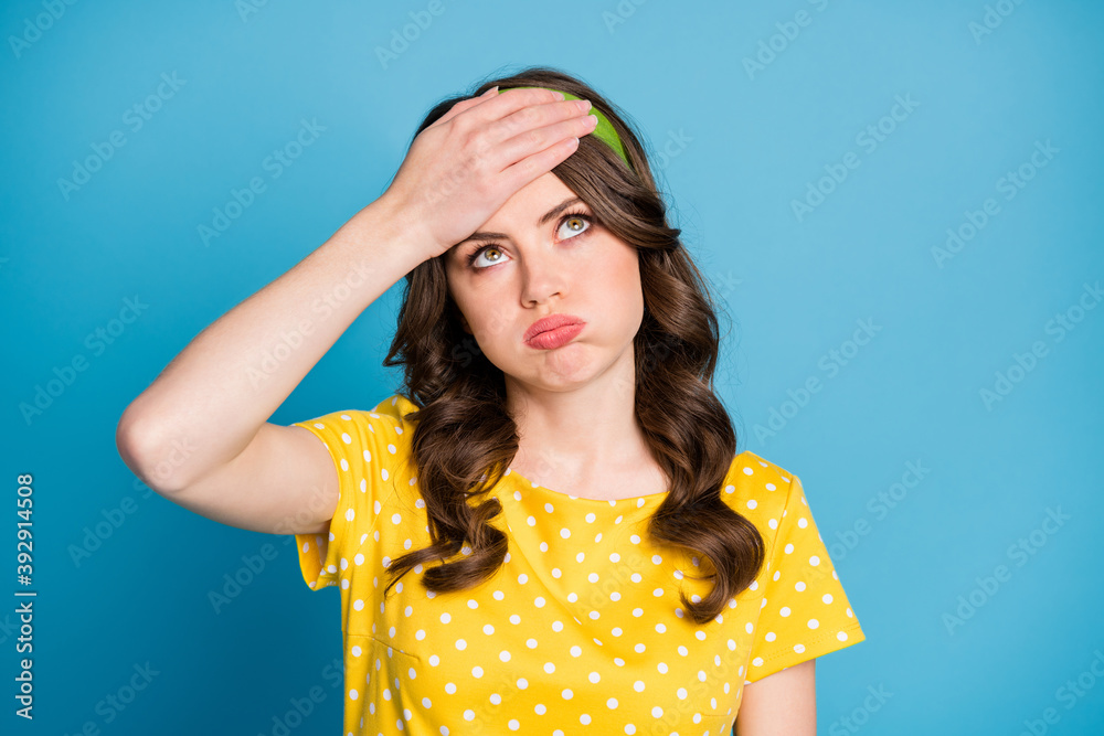 Fototapeta Frustrated tired girl touch forehead with hand look copyspace sigh wear yellow green clothes isolated on blue color background