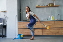 Happy Worker. Full Length Shot Of Cheerful Young Woman, Cleaning Lady Pretending To Sing A Song, Holding Broom While Cleaning The Floor, Doing Household Chores