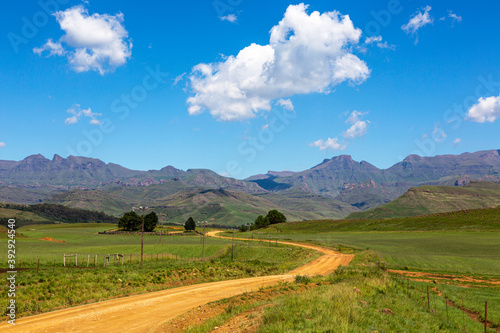 Gravel road through green pastures to the mountain Fotobehang