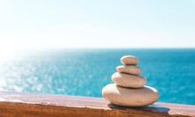 Zen Relax Background. A Pyramid Of Stones On The Beach In Clear Sunny Weather. Background For Meditation, Yoga And Massage