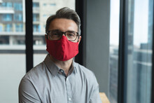Portrait Of Caucasian Man Wearing Face Mask At Modern Office