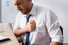 Businessman Having Heart Attack, While Sitting At Workplace On Blurred Background