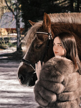 A Girl In A Beautiful Dress And Fur Coat With A Horse Stands Near The